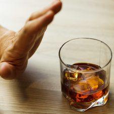 Mano rechazando un vaso de whisky